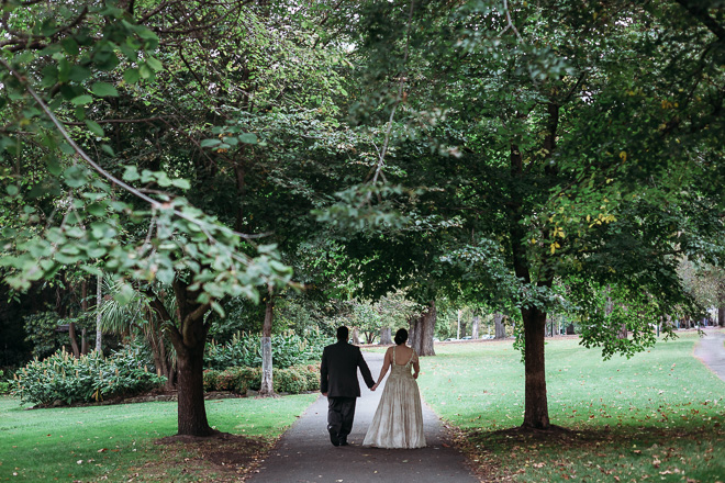 bride and groom walk through the park under the tree